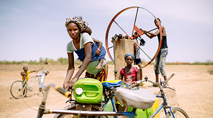 A woman bicycles with her baby to fetch water for her family, Sorobouly village near Boromo, Burkina Faso.© Ollivier Girard/ Center for International Forestry Research