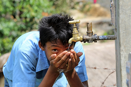 A boy drinks water from a tap stand at his school in Puware Shikhar, Udayapur District, Nepal © Jim Holmes / AusAID